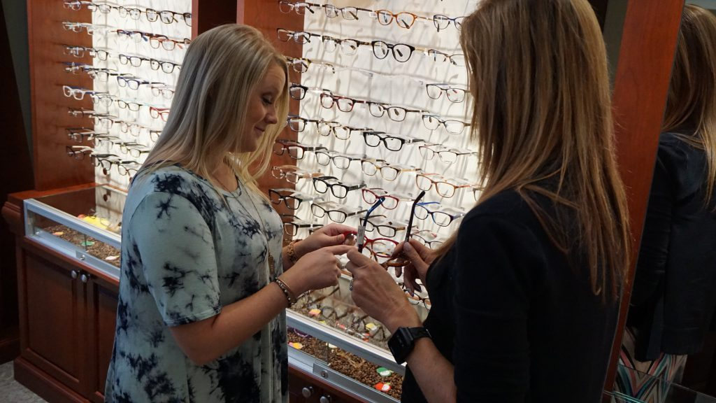 Optician helping patient select eyeglasses