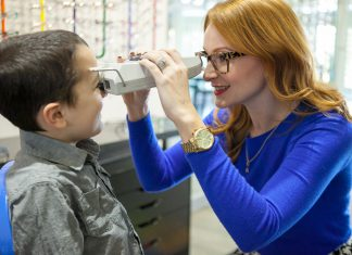 An optician taking the pupillary distance (pd) of a child using a pupilometer.