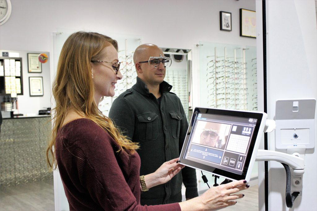An optician taking an adult's progressive eyeglasses measurements.