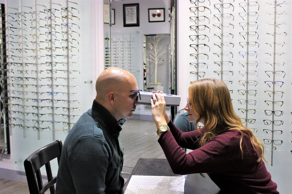 An optician taking an adults pupillary distance (pd)