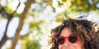 Woman-smiling-wearing-Transitions-Lenses-outdoors.
