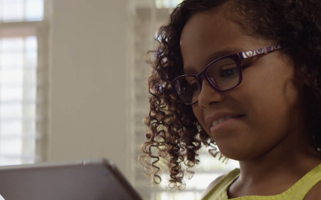 Girl wearing transitions lenses on a tablet.