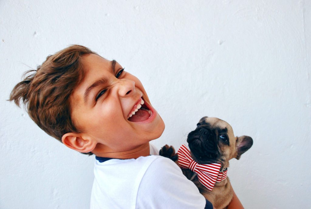 Young boy exhibiting emotional wellness as he smiles and holds a little dog