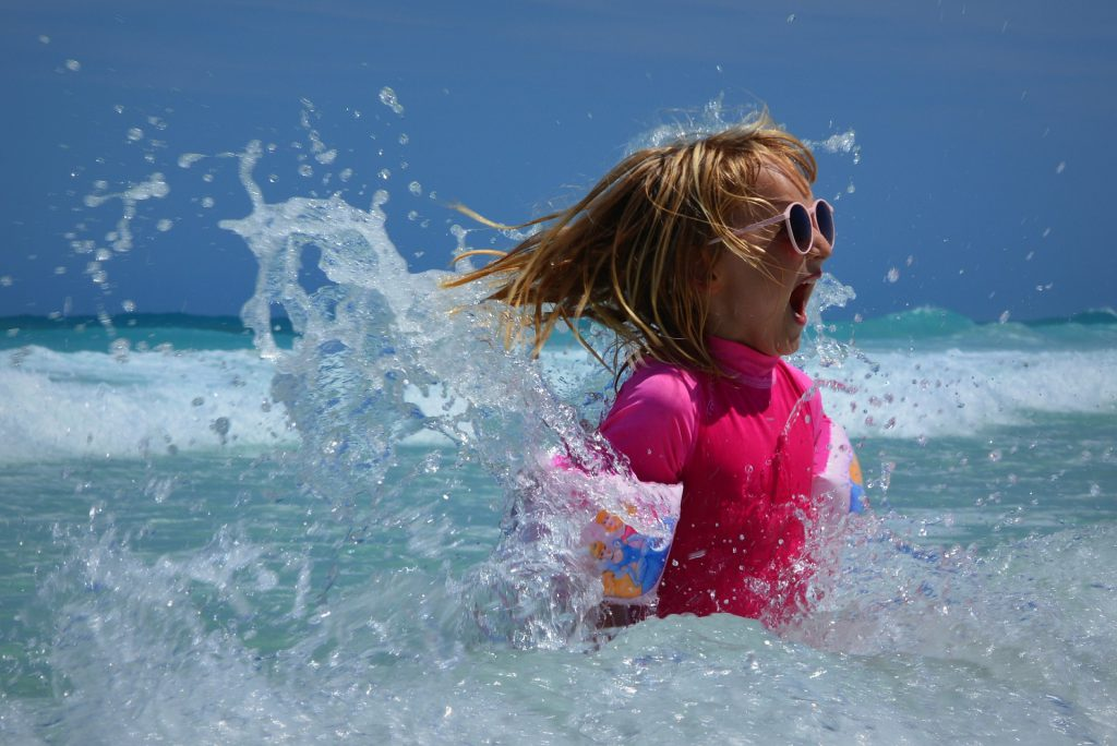 Little girl wearing sunglasses in the ocean