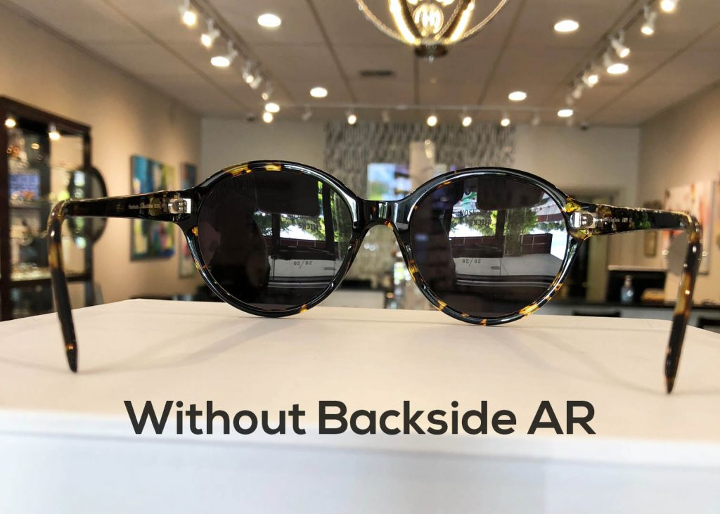 Sunglasses without a backside anti-reflective coating
